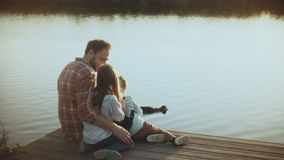 Caucasian man with two children watch water birds. Happy dad and kids sit together on a sunset lake pier. Childhood. 4K. Caucasian man with two children watch stock video footage