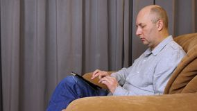 Caucasian man typing at tablet. Adult man sits on armchair. Home interior stock footage