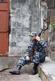 Caucasian man in urban warfare sitting with rifle protecting gat Royalty Free Stock Images