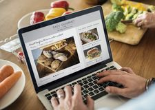 Caucasian man using a laptop in the kitchen searching for recipes royalty free stock images