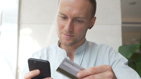 Caucasian man using mobile phone for online shopping with credit card stock video footage