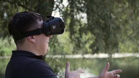 Caucasian man in vr glasses outdoors in the park playing game or working as an architector. Future stock footage