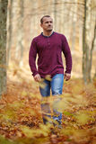 Caucasian man walking in the forest. Caucasian man taking a walk in the forest, autumnal landscape Royalty Free Stock Image