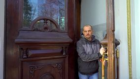 Caucasian man walks out of massive wooden door of historic building. Architecture, city life, cultural heritage stock footage