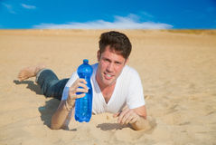 Caucasian man with water in desert Stock Photo