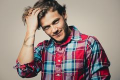 Caucasian man wearing checkered shirt and trendy hairstyle. Fashion portrait of a handsome man with trendy hairstyle in a stylish shirt on light green background Stock Images