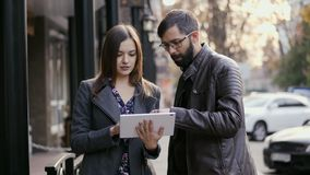 Caucasian man and woman standing with tablet device in hands on the street, speak and watching something. stock video footage