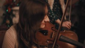 String quartet violins playing music in room with christmas decorations. Caucasian man and woman string quartet violins joyfully playing music in room with stock video footage