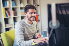 Caucasian man at work desk facing flat screen computer. Handsome Caucasian man at work desk facing flat screen computer screen in office Stock Photo