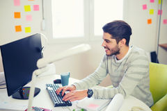 Caucasian man at work desk facing flat screen computer. Handsome Caucasian man at work desk facing flat screen computer screen in office Stock Photography