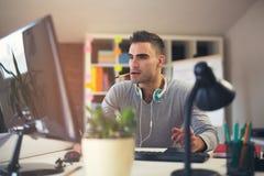 Caucasian man at work desk facing flat screen computer. Handsome Caucasian man at work desk facing flat screen computer screen in office Stock Photos