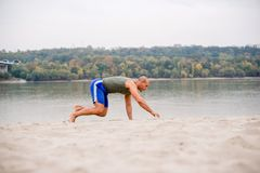 Caucasian man work out on beach. Summer time Stock Image