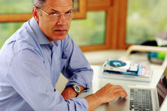 Caucasian man working on his laptop computer Stock Images