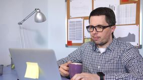 Caucasian man working in the office, he drinking coffee while working. stock video