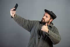 Caucasian man 35 years old doing selfie, studio shot. Idea - village dweller and modern technology royalty free stock images