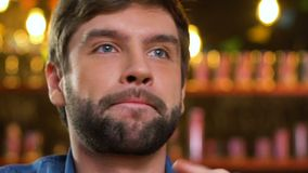 Caucasian manlig fanrubbning om domarebeslutet, hållande ögonen på fotbollsmatch i bar arkivfilmer