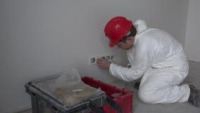 Caucasian manlig montering för vägg för uttag för elektrikerbeslaghålighet i nybygge arkivfilmer