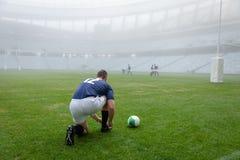 Caucasian manlig rugbyspelare som binder skosnöre i stadion royaltyfri foto