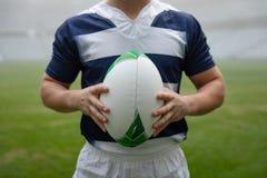 Caucasian manlig rugbyspelare som rymmer en rugbyboll i stadion royaltyfri fotografi