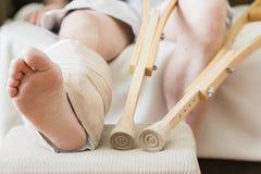 Caucasian manlig ` s sårade benet på fotapallen med kryckor bredvid stolen Arkivfoton