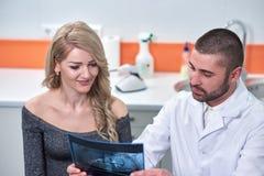 Caucasian manlig tandläkare som förklarar till den kvinnliga patienten röntgenstrålen arkivfoton
