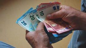 Caucasian manliga händer som räknar upp eurosedlar, sikt från det tillbaka slutet arkivfilmer