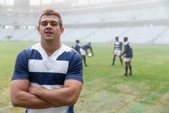 Caucasian manligt rugbyspelareanseende med armar som korsas i stadion arkivbild