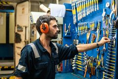 Marine engineer officer working in engine room. Caucasian marine engineer officer in engine control room ECR. He works in workshop and chooses correct tools and royalty free stock photos