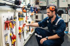 Marine engineer officer working in engine room. Caucasian marine engineer officer in engine control room ECR. He works in workshop and chooses correct tools and royalty free stock image