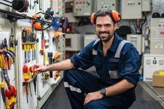 Marine engineer officer working in engine room. Caucasian marine engineer officer in engine control room ECR. He works in workshop and chooses correct tools and stock images