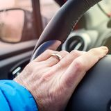 Holding driving wheel with left hand. Caucasian married man is holding driving wheel  with left hand Royalty Free Stock Photo