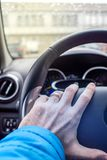 Holding driving wheel with left hand. Caucasian married man is holding driving wheel  with left hand Stock Photo