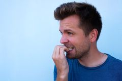 Caucasian mature man gnawing nails. Bad habit when you fell nervous and worry a lot. Neurotic type of personality Stock Image