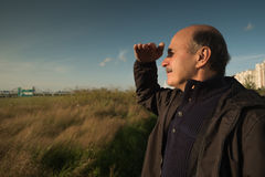 Caucasian mature man looking at the horizon. Trying to see something at the distance Royalty Free Stock Images