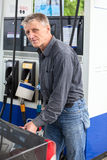 Caucasian mature man refueling car Stock Images