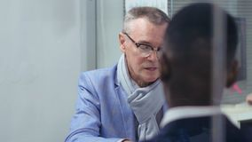 Caucasian mature man in travel agency. Caucasian mature man in glasses sitting in travel agency paying for package tour using his credit card stock footage