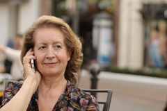 Caucasian mature woman calling by phone outside.  Stock Photo