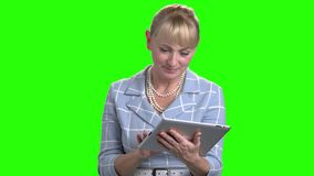 Caucasian mature woman using digital tablet. Pretty business woman working on computer tablet on chroma key background. People, technology and lifestyle stock video