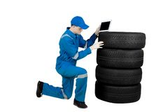 Caucasian mechanic checks tire with a tablet. Picture of Caucasian man mechanic using a digital tablet for check a pile of tires, isolated on white background Stock Image