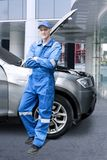 Caucasian mechanic leaning with a car. Portrait of Caucasian male mechanic folded his arms while leaning with a car. Shot at outdoor Stock Images