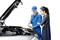 Caucasian mechanic talking with client on studio. Caucasian male mechanic is checking broken car by using a tablet while talking to his client, isolated on white Stock Photography