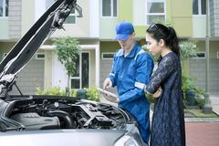 Caucasian mechanic talking with his client. Image of Caucasian male mechanic checking broken car by using a tablet while talking to his client Stock Photography