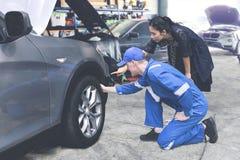 Caucasian mekaniker som hjälper en kvinnlig klient att kontrollera på ett däck fotografering för bildbyråer