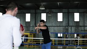 Caucasian men in casual clothes throwing heavy ball to each other while doing punces. Two young boxers training upper. Body and arms. Workout exercises together stock video footage