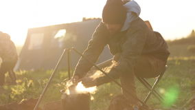 Caucasian men cooking food in boowler at bonfire in camping. stock video footage