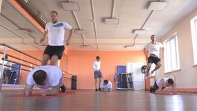Caucasian men in group doubles in a modern fitness center perform jumping exercises to lose weight and promote health. Group training, sportswear, beautiful stock footage