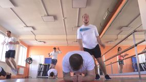 Caucasian men in group doubles in a modern fitness center perform jumping exercises to lose weight and promote health. Group training, sportswear stock footage