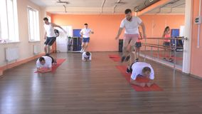 Caucasian men in group doubles in a modern fitness center perform jumping exercises to lose weight and promote health. Group training, sportswear stock video
