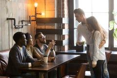 Caucasian man introducing girlfriend to friends at cafe. Caucasian men introducing girlfriend to multiracial millennial friends sitting at table, enjoying coffee stock photo