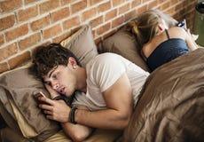 Caucasian man using mobile phone in bed stock image